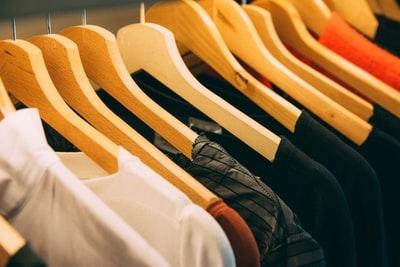 ハンガーにかかった多くの衣服の写真
